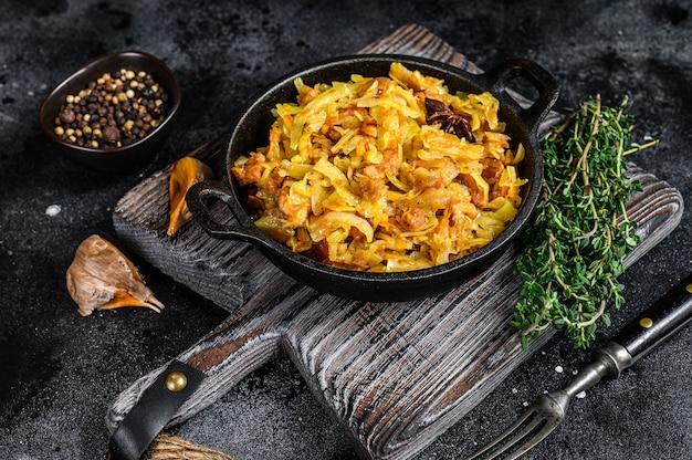 Geschmorter kohl bigos mit pilzen und würstchen