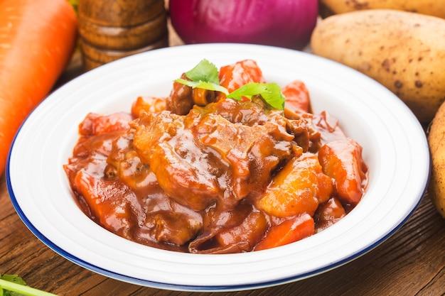 Geschmorter rindfleischschwanz mit karotten und kartoffeln