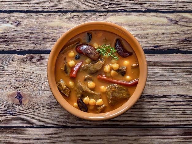 Geschmortes fleisch mit bulgur und kichererbsen in roter sauce mit datteln und rosinen.