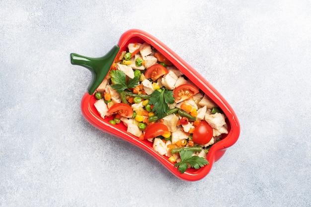 Geschmortes hühnerfleisch mit gemüse karotten paprika erbsen mais in einem teller in form von rotem pfeffer. speicherplatz kopieren.