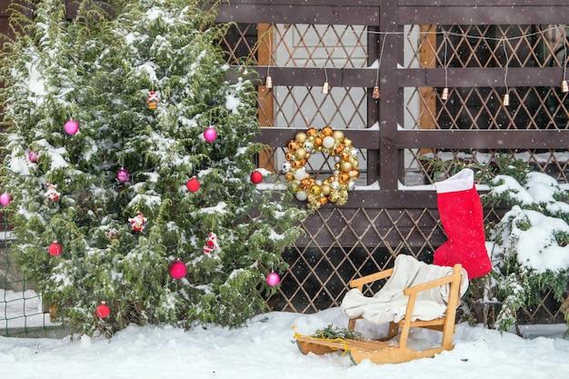 Geschmückt für weihnachten veranda eines wohnhauses im winter bei schneefall