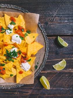 Geschmückte geschmackvolle mexikanische nachos in der platte mit zitronenscheiben auf holztisch