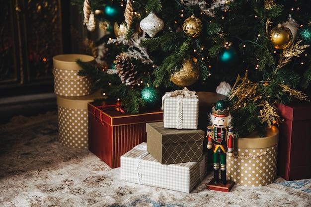 Geschmückter neujahrsbaum und viele geschenke darunter. weihnachtsbaum mit vielen bunten dekorationen