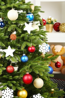 Geschmückter weihnachtsbaum auf innenhintergrund