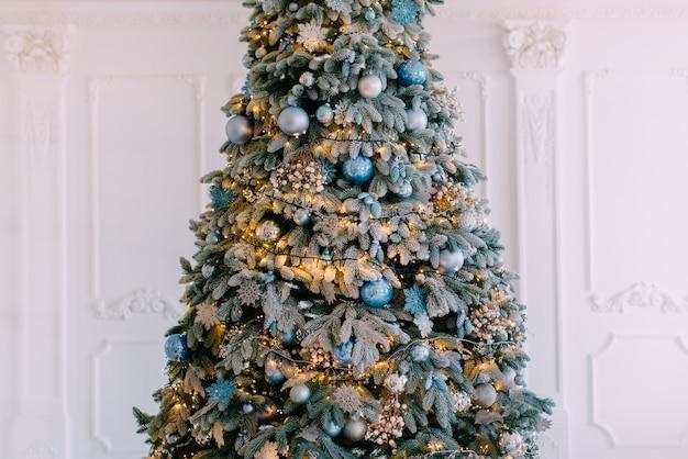 Geschmückter weihnachtsbaum auf weißem wandhintergrund, nahaufnahme