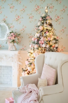 Geschmückter weihnachtsbaum im klassischen interieur mit kamin und sessel.