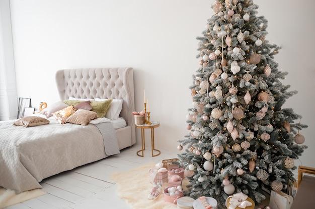 Geschmückter weihnachtsbaum im zimmer mit bett.