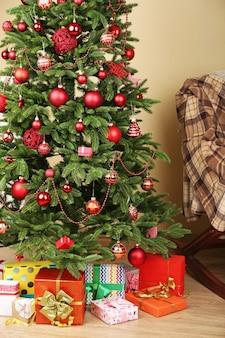 Geschmückter weihnachtsbaum mit geschenken in der raumnahaufnahme