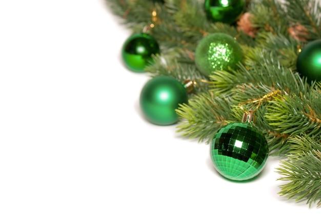 Geschmückter weihnachtsbaum mit grünen kugeln auf weißem hintergrund isoliert