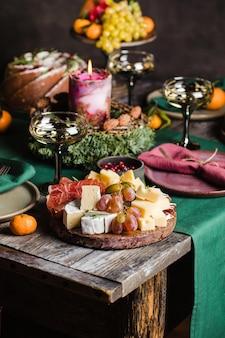 Geschmückter weihnachtstisch serviert für personen käseplatte mit traubenschinken kerzenkuchen hochwertige ...
