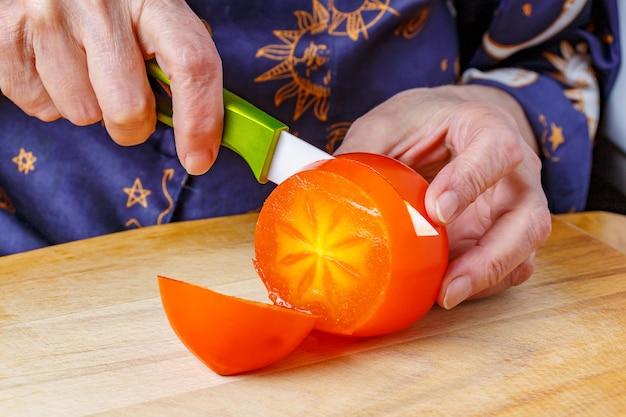 Geschnitten von keramikmesser saftige reife persimone in der hand der älteren frau