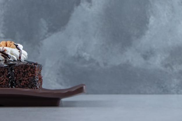 Geschnitten von leckerem schokoladenbrownie mit sahne auf dunklem teller. foto in hoher qualität