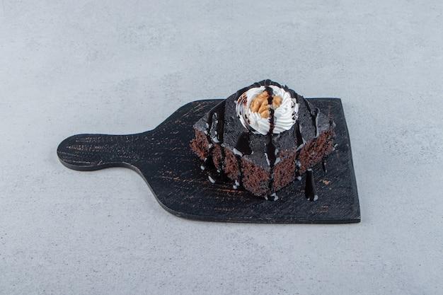Geschnitten von leckerem schokoladenbrownie mit sahne auf schneidebrett. foto in hoher qualität