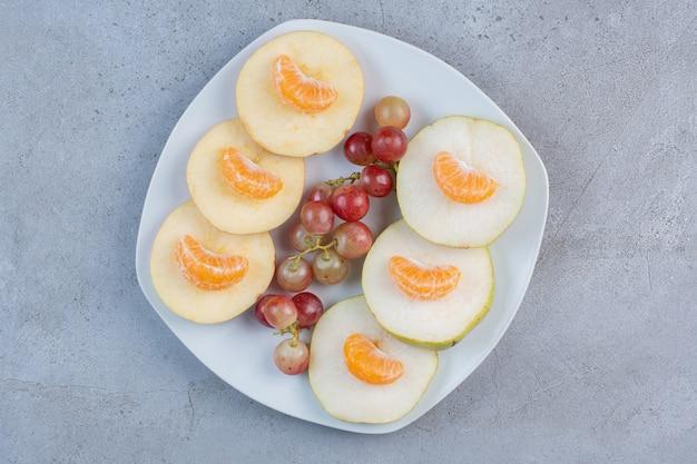 Geschnittene äpfel, birnen, mandarinen und trauben auf einer platte auf marmorhintergrund.