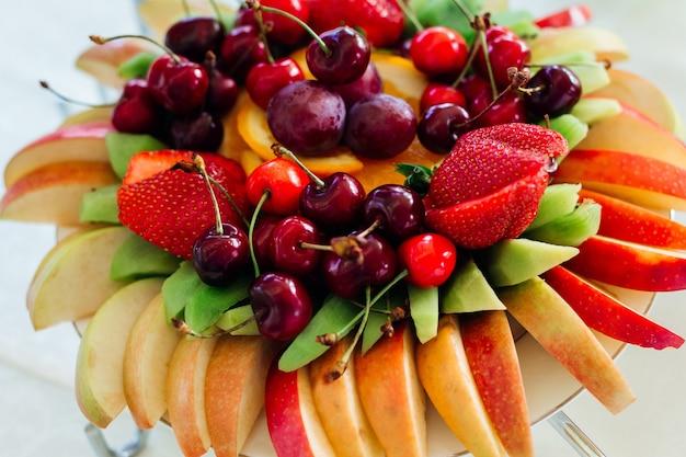 Geschnittene äpfel, kiwi, erdbeeren und kirschen liegen serviert