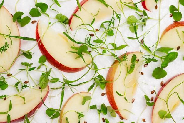 Geschnittene äpfel mit jungen mikrogrünen sprossen auf weißem hintergrund, gesunde ernährung. flach liegen. weißer hintergrund