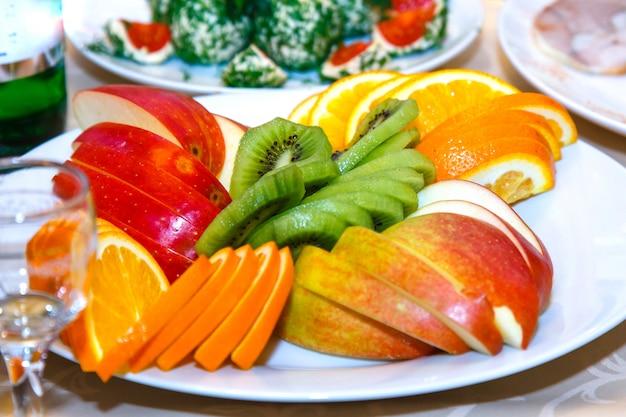 Geschnittene äpfel, orangen auf einem banketttisch