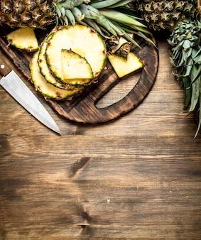 Geschnittene ananas auf schneidebrett mit einem messer auf holztisch.