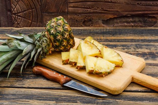Geschnittene ananas in einem schneidebrett mit einer obstmesserseitenansicht auf einer holzschmutzfläche und einer steinfliese