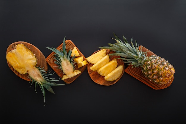 Geschnittene ananas in verschiedenen formen. reife ananas auf dem schneidebrett, das sommerdessert auf schwarzem hintergrund kocht. flache lage hochwertiges stockfoto