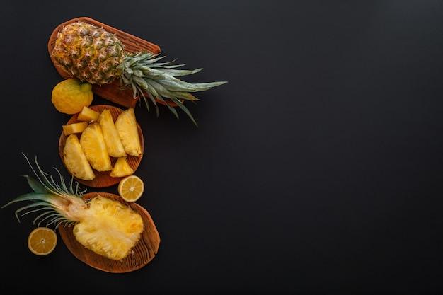 Geschnittene ananas in verschiedenen formen. reife ananas auf dem schneidebrett, das sommerdessert auf schwarzem hintergrund kocht. flache lage mit kopienraum.