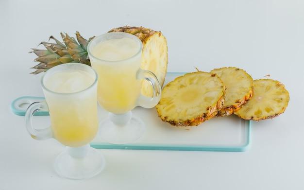 Geschnittene ananas mit säften auf schneidebrett