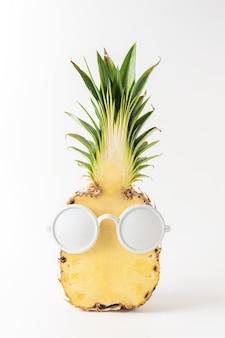 Geschnittene ananas mit weißer sonnenbrille auf weißem hintergrund.