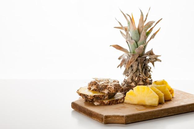 Geschnittene ananasscheiben auf einem küchenbrett