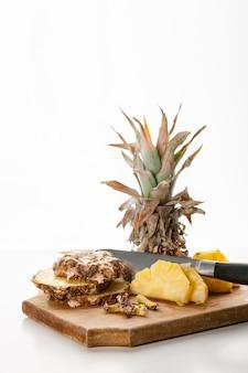 Geschnittene ananasscheiben mit einem messer auf einem küchenbrett