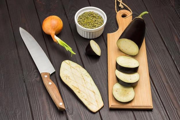 Geschnittene auberginen auf schneidebrett mungbohnengrütze in schüssel messer und bogen auf tisch