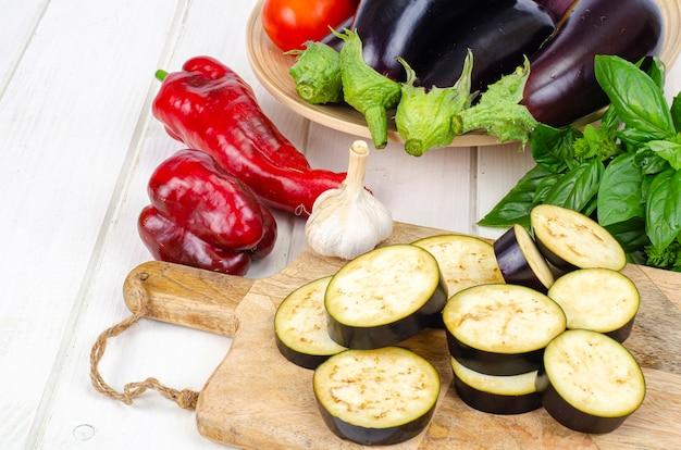 Geschnittene auberginenscheiben auf holzbrett, gemüse der saison zum kochen. studiofoto.