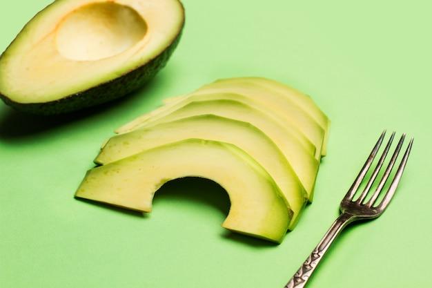 Geschnittene avocado mit einer gabel auf grünem hintergrund