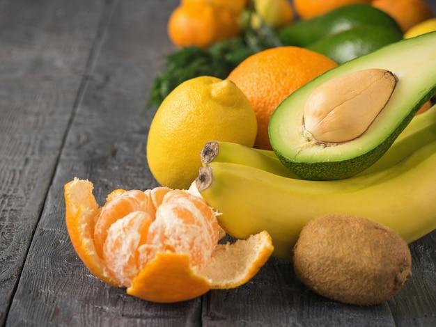 Geschnittene avocado, tangerinen, orangen, kiwi und bananen auf rustikaler tabelle der weinlese. vegetarisches essen.