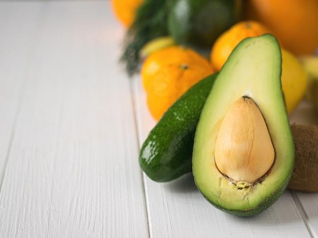 Geschnittene avocado, tangerinen, orangen, kiwi und bananen auf weinleseweißtabelle. vegetarisches essen.