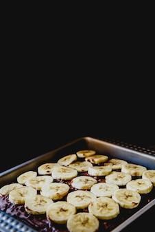 Geschnittene banane auf einem kuchen auf einem tablett vor dem backen.