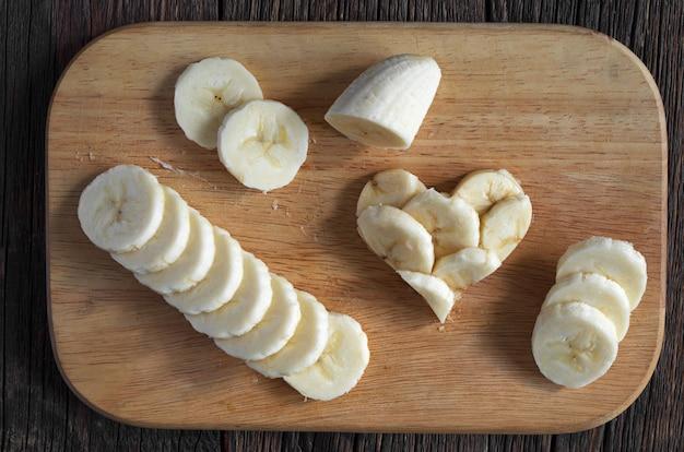 Geschnittene bananen und form der herzen auf holzschneidebrett