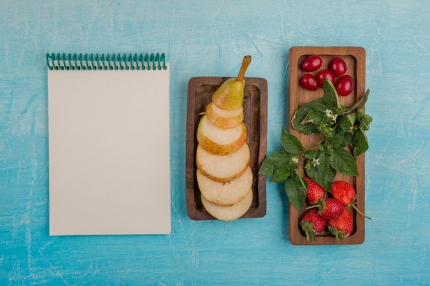 Geschnittene birnen mit erdbeeren und maulbeeren in holzplatten mit einem notizbuch beiseite