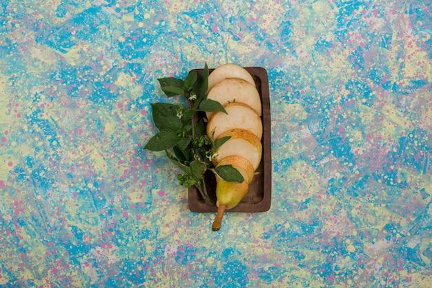 Geschnittene birnen, serviert mit minzblättern auf einer holzplatte in der mitte