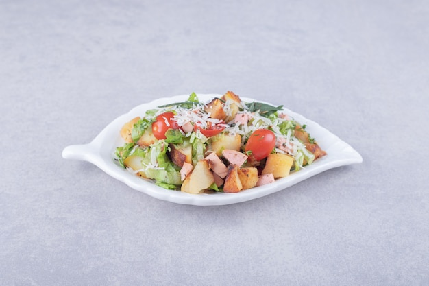 Geschnittene bratwürste und salat in weißer schüssel.