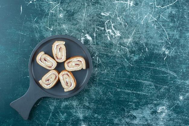 Geschnittene brötchenkuchen auf einer pfanne, auf der blauen oberfläche