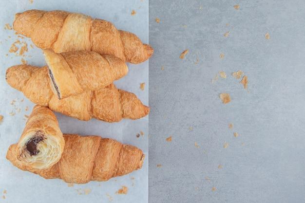 Geschnittene croissants auf papier, r auf dem marmorhintergrund. hochwertiges foto