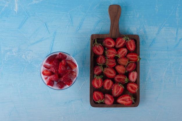 Geschnittene erdbeeren in einer glasschale und auf dem holzschneidebrett