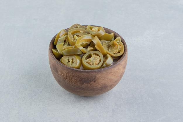 Geschnittene essiggurken-jalapeno-paprika in einer schüssel, auf der marmoroberfläche