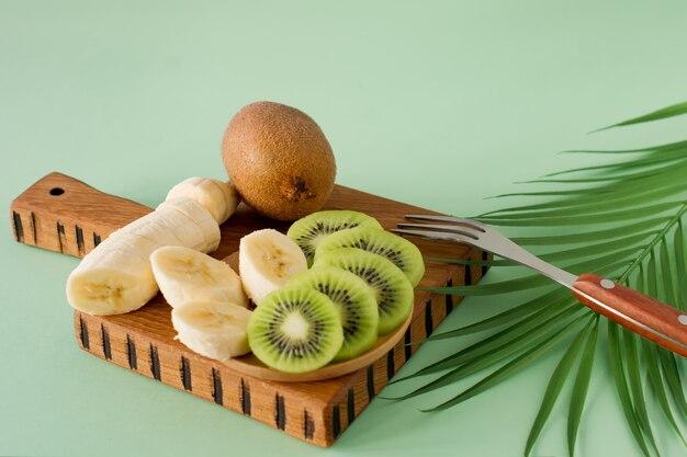 Geschnittene exotische früchte auf einem holzbrett, nahaufnahme. kiwi und banane in scheiben geschnitten zum kochen von smoothies. reich an vitaminen und frischem obst, gesunde bio-lebensmittel.