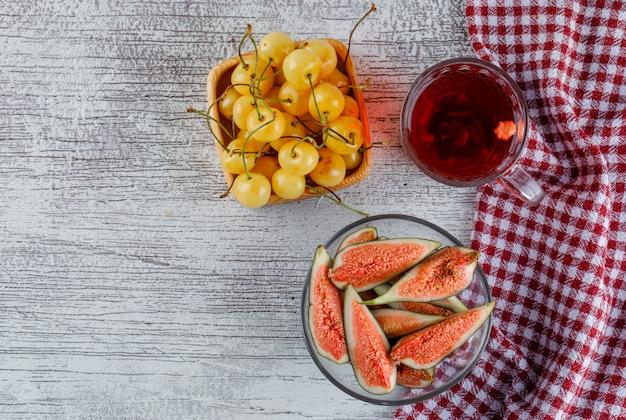 Geschnittene feigen in einer schüssel mit kirschen, tasse tee draufsicht auf grungy und küchentuch