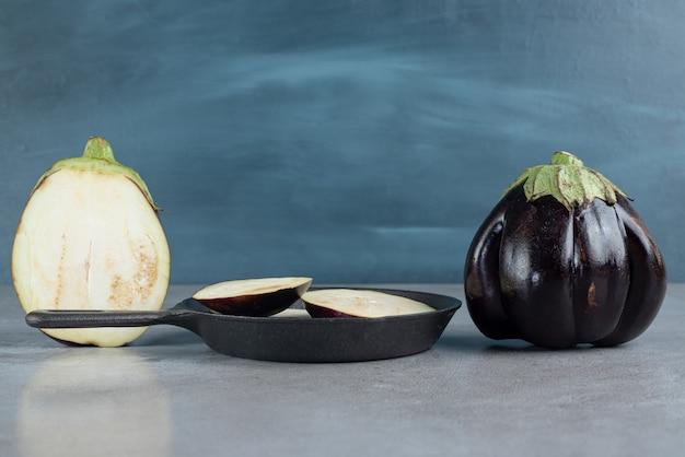 Geschnittene frische auberginen auf grauem hintergrund. foto in hoher qualität