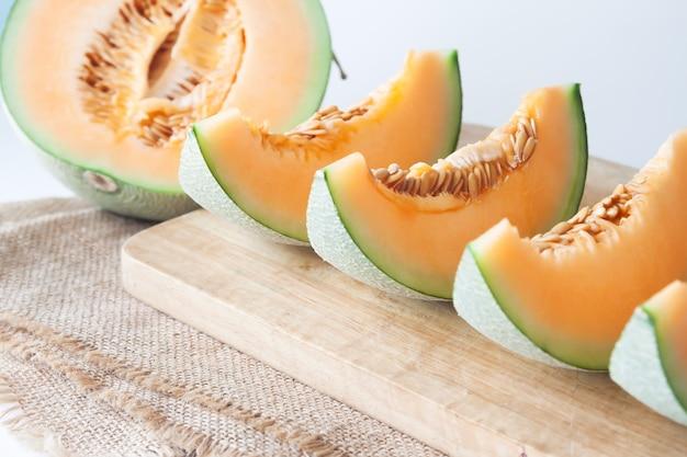 Geschnittene frische japanische melone, orange melone auf schneidebrett. selektiver fokus