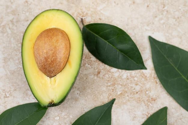 Geschnittene frische köstliche avocado auf marmorhintergrund.