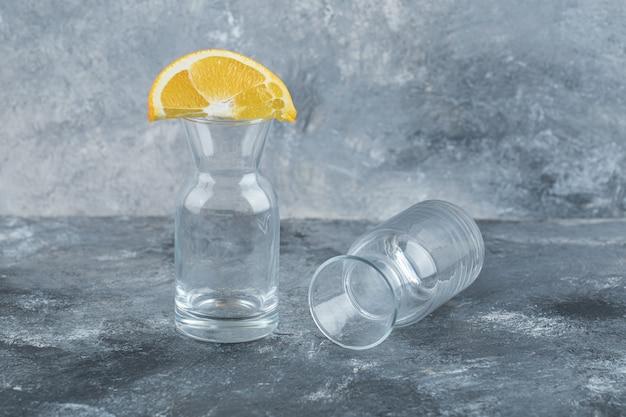 Geschnittene frische orange auf leeres glas.