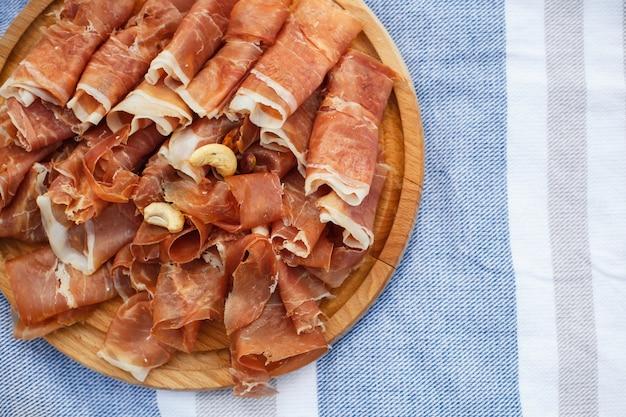 Geschnittene frische rollen von jamon auf hölzernem behälter an der picknickdecke. sommerwochenenden